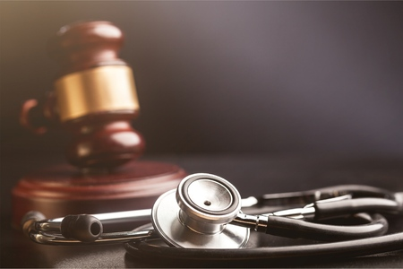 Gavel and stethoscope on wooden background, symbol