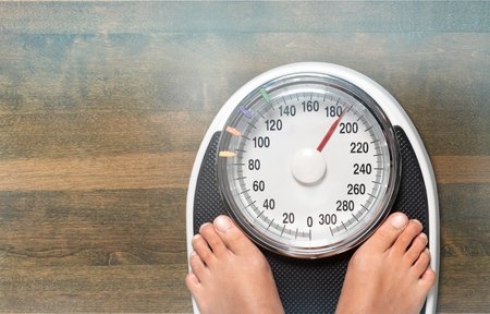Male on the weight scale for check concept