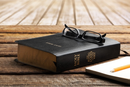 holy bible with eye glasses on table Stock Photo