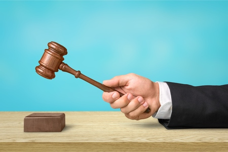 A businessmans hand holding a justice gavel