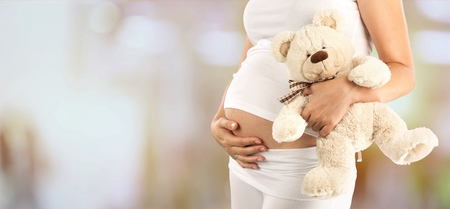 A pregnant woman holding a stuffed bear