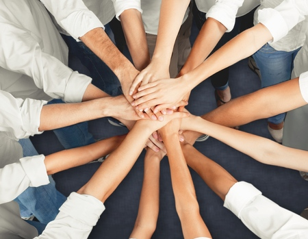 Handshake of many young business people, teamwork