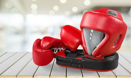Red boxing gloves on wooden background