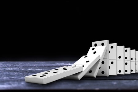 White Dominoes falling on a wooden desk Stock Photo