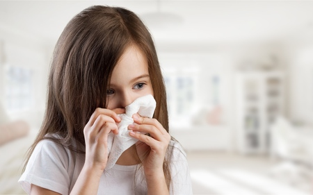 A little girl getting a cold and blowing her nose Stock Photo