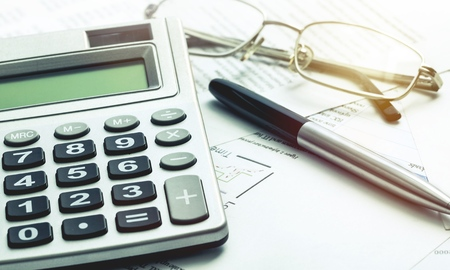 Calculator, pen, glasses and the financial report