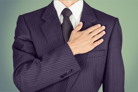 Business man holds hand on heart