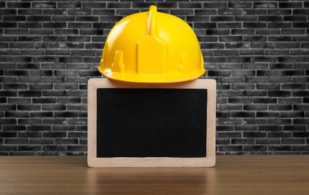 Safety helmet and black board on a wooden table.