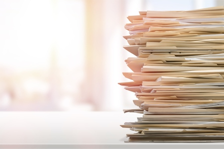 Stack of report paper documents in office