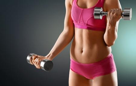 Torso of a young fit woman lifting