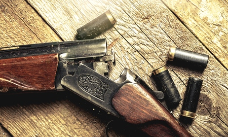 Vintage rifle and sleeves on wooden table