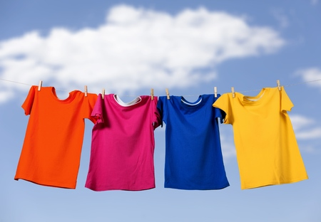 Colorful T-shirts hanging on a rope on 写真素材