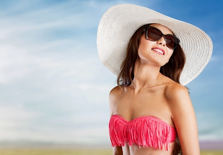 Beautiful woman in swimsuit sunglasses and hat