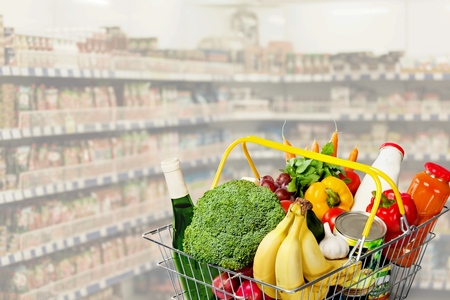 Shopping basket with variety of grocery products Stock Photo