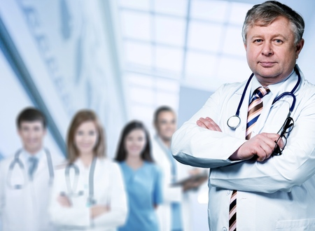 Male doctor with stethoscope smiling at camera
