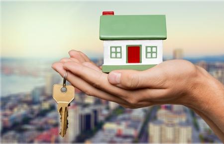 Businessman Holding House Model and Keys Stock Photo