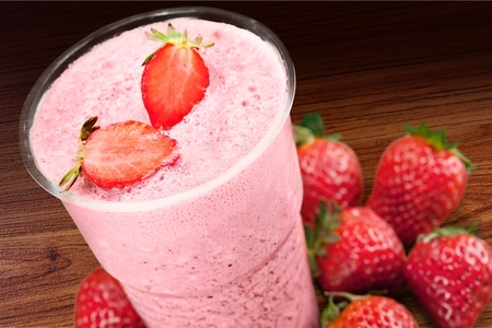 Glass of strawberry smoothie on wooden table