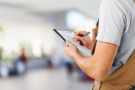 Closeup of a worker with list checking