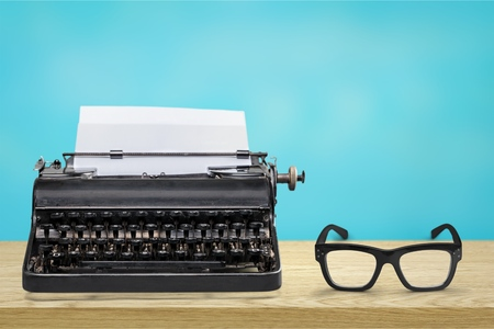 Retro black typewriter and spectacles on wooden Foto de archivo