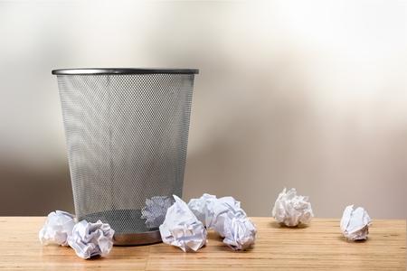 Pattumiera con fogli di carta su legno