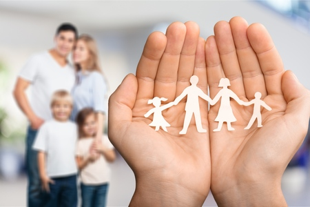 Hands with family of paper people on