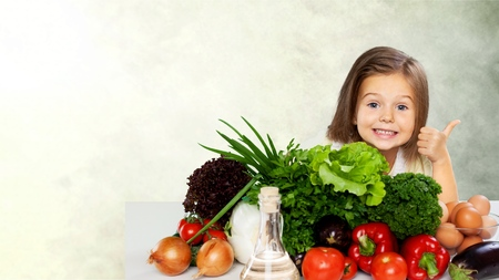 Cute little girl with vegetables in kitchen