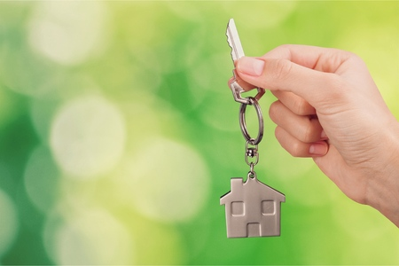 Home key in house keychain on woman
