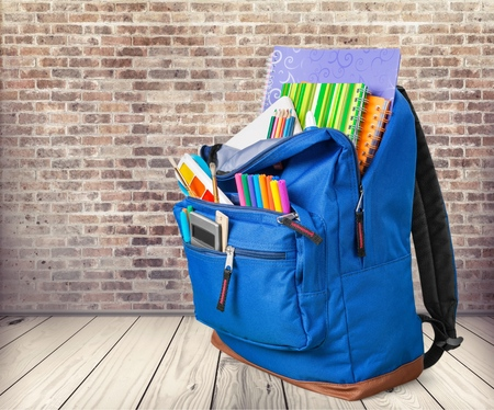 Open red school backpack on wooden table