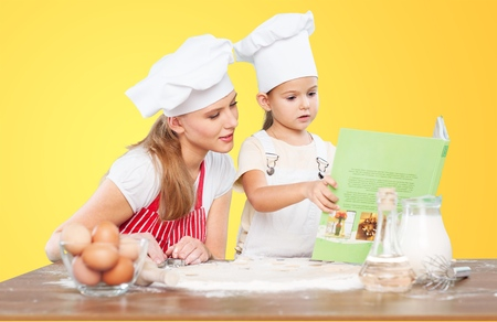 beautiful housewife cooking with ladle and cookbook