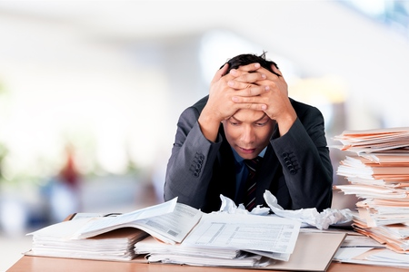 Surprised young businessman with stack of papers