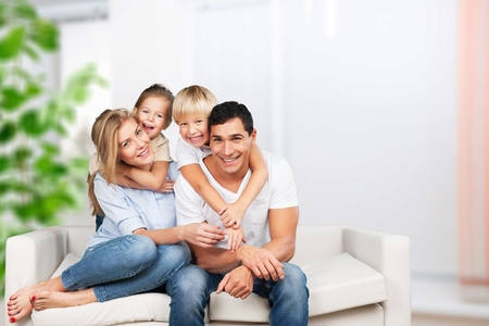Hermosa familia sonriente sentada en el sofá en casa