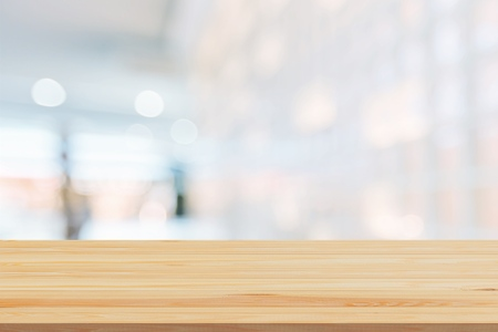Wood table top on blur white glass wall background form office building.For montage product display and design key visual layout - Image