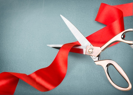 Scissors cutting red ribbon, close-up view on blue background 版權商用圖片