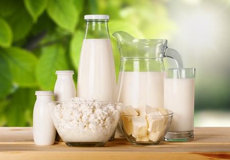 Vaso de leche y productos lácteos en el fondo