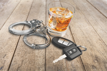 Whiskey with car keys and handcuffs concept for drinking and driving 免版税图像
