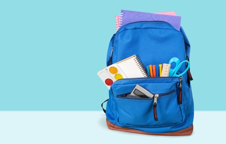 School Backpack with stationery on background