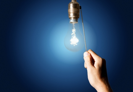 Hand turning off the bulb lamp.Turning off
