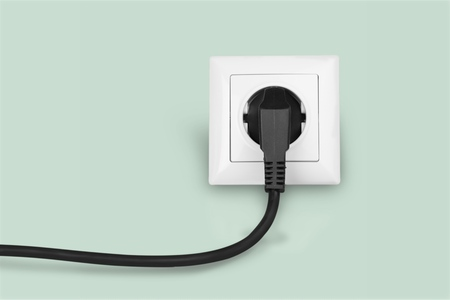 White electrical plug in the electric socket on a wall Banco de Imagens