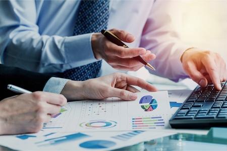 Zusammenfassung des Berichtsdiagramms zur Analyse der Unternehmensgründung und Verwendung eines Taschenrechners zur Berechnung der Zahlen. Standard-Bild
