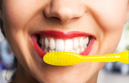 Female brushing teeth with yellow brush, close up 免版税图像