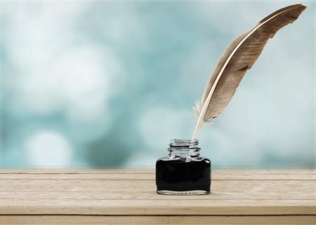 Pluma pluma y tintero de vidrio aislado sobre un fondo blanco.