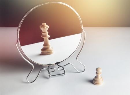 Peón de ajedrez mirándose al espejo y viendo una reina
