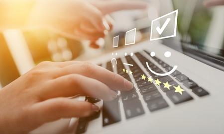 Empresaria presionando smiley en el teclado del ordenador portátil. Concepto de evaluación de servicio al cliente. Foto de archivo