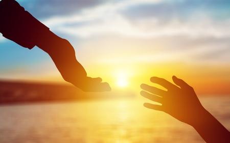 Help hand on sunset background Stockfoto