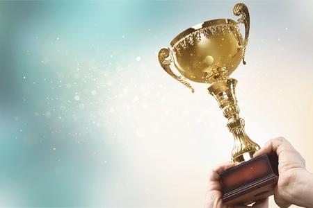 Manos sosteniendo el trofeo de oro sobre un fondo claro Foto de archivo