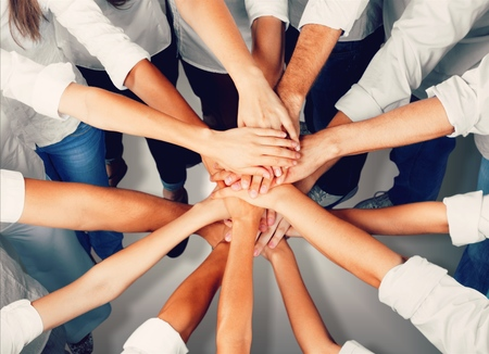 Group of people stacking hands together Imagens