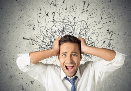 Sad young man with worried stressed face expression and brain melting into lines question marks. Obsessive compulsive, adhd, anxiety disorders concept Stock Photo
