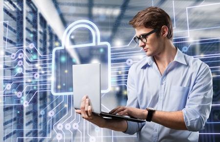 Joven ingeniero de TI hombre de negocios con delgado y moderno portátil de aluminio en la sala de servidores de red Foto de archivo