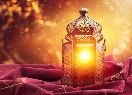 Ornamental silver Moroccan, Arabic lantern on white linen throw. Burning candle, glittering bokeh lights. Greeting card for Muslim community holy month Ramadan Kareem. Festive background.