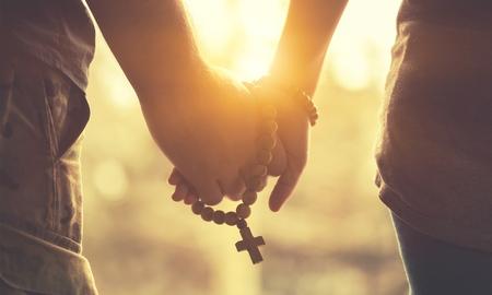Paar samen bidden. Rozenkrans in de hand houden.